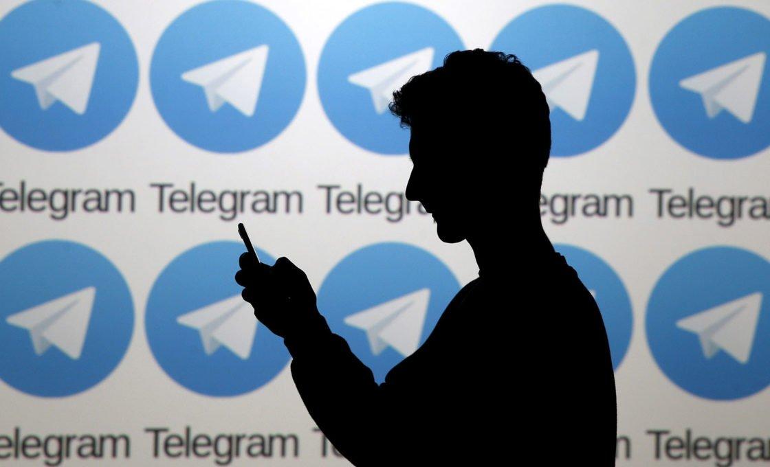 Силуэт человека со смартфоном на фоне баннера Telegram
