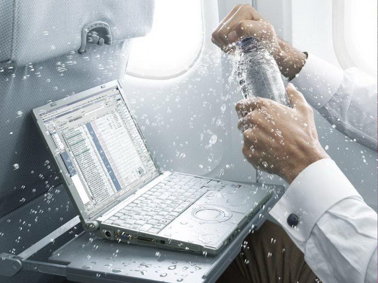 Мужчина открывает бутылку с водой над ноутбуком