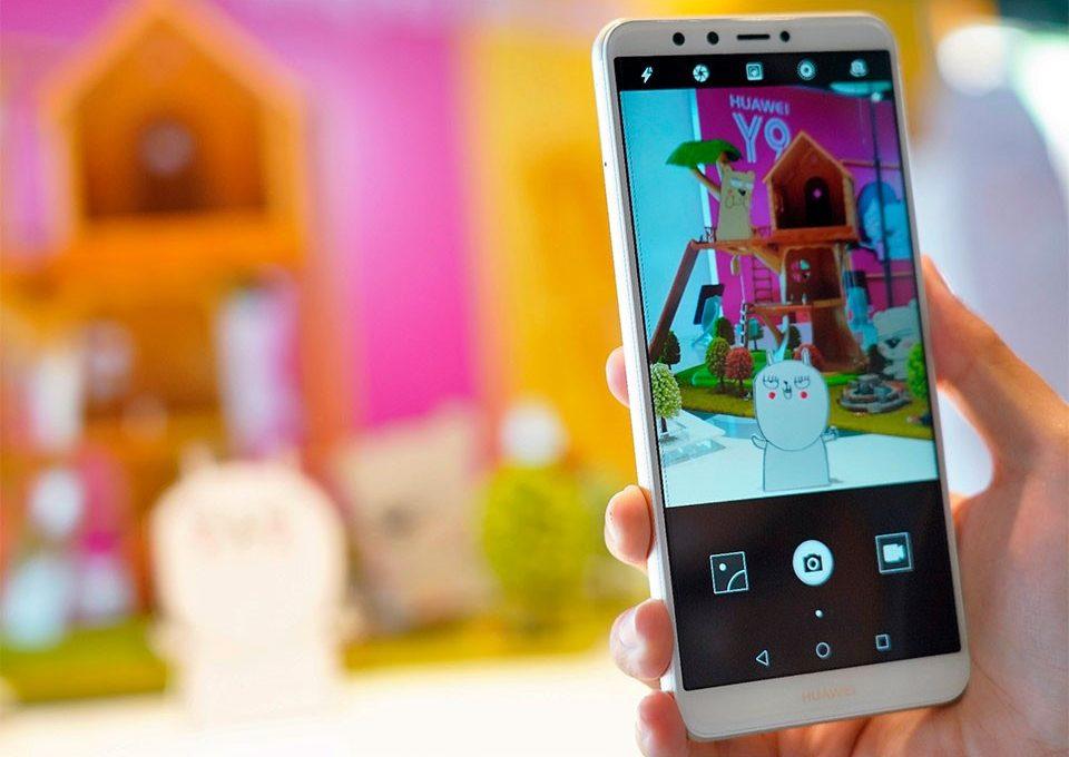 Человек с телефоном Huawei Y9 в руке делает фото
