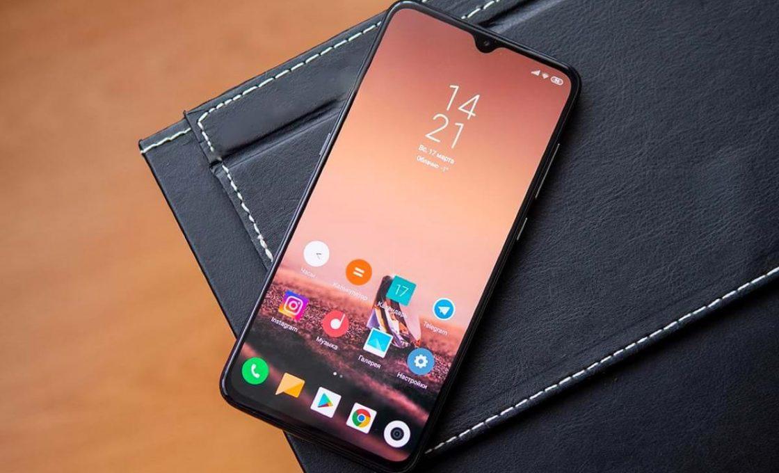 Мобильный телефон Xiaomi Mi 9 лежит на тёмной обложке