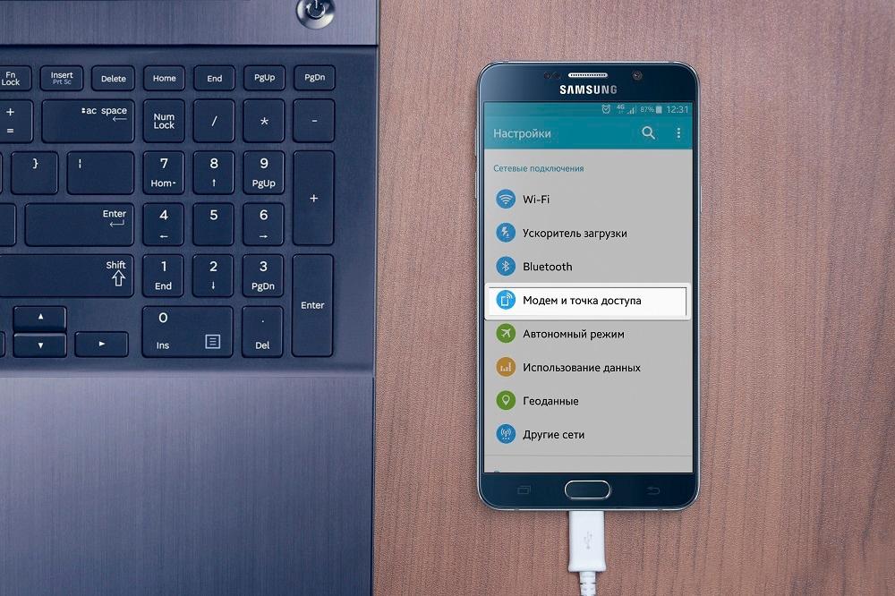 Телефон Samsung лежит рядом с ноутбуком