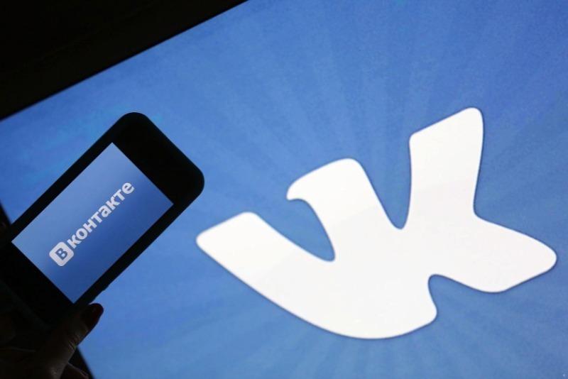 Рука держит телефон на фоне большого логотипа ВКонтакте