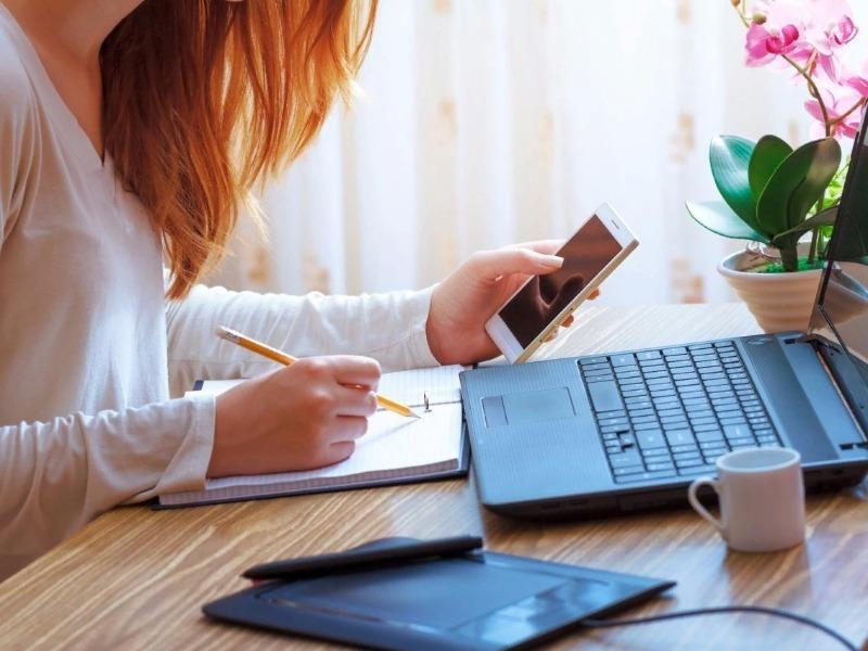 Девушка с телефоном в руке сидит за ноутбуком и делает записи в блокноте