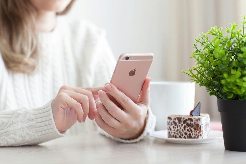 Девушка в белом свитере с айфоном в руке за столиком в кафе