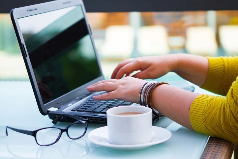 Девушка работает за ноутбуком, рядом на столе очки и чашка